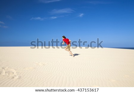 Fuerteventura sand dunes in the north of the island, teenage boy in red t-shirt and shorts running  - stock photo