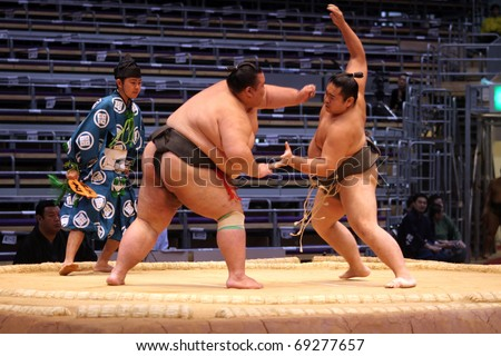 FUKUOKA, JAPAN - NOVEMBER 19: Unidentified Sumo wrestlers trying to grab each other in the Fukuoka Tournament on November 19, 2010 in Fukuoka, Japan. - stock photo