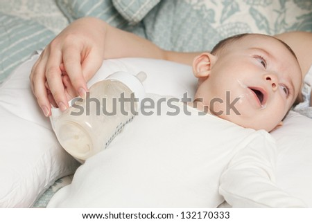 Full baby with the milk on his mouth and empty bottle aside - stock photo