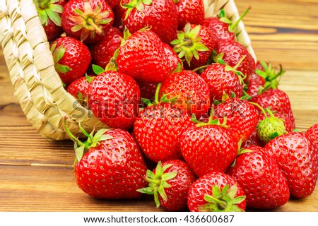 Full basket of ripe strawberries that are poured out on the wooden table - stock photo