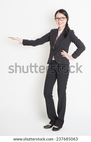 Full body Asian business woman showing copy space, hand holding something, standing on plain background. - stock photo
