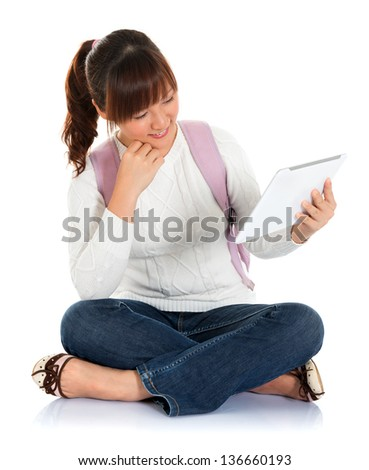 Full body Asian female young adult student sitting on floor using tablet pc isolated on white background - stock photo