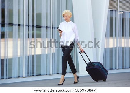 Full body business woman traveling with suitcase and mobile phone - stock photo