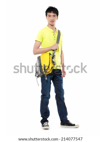 Full body casual man wearing yellow t-shirt and jeans carrying a bag  - stock photo