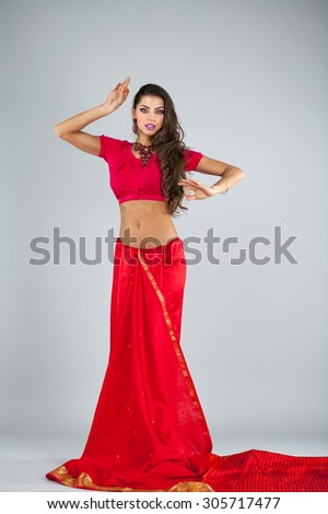 Full body cheerful traditional Asian Indian woman in indian sari, isolated on gray background - stock photo