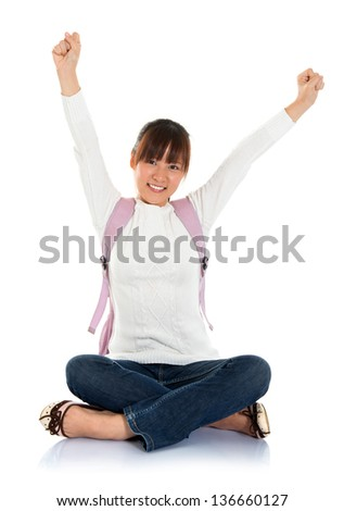 Full body excited Asian female young adult student sitting on floor hand raised arms up isolated on white background - stock photo