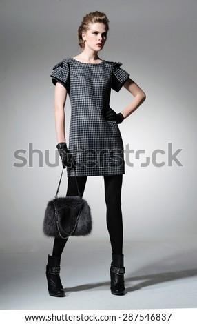Full body fashion model clothes holding handbag posing-gray background - stock photo