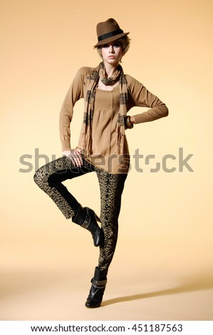 Full body fashion model in fashion dress with hat, scarf posing in light background - stock photo