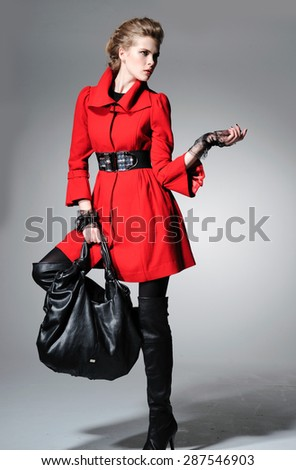 Full body fashion model red clothes holding black handbag posing-gray background - stock photo