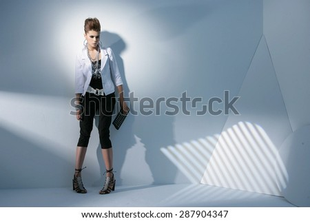 Full body fashion model wearing modern holding purse posing in light background - stock photo