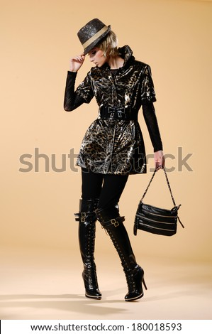 Full body fashionable woman in a hat posing holding handbag on beige background - stock photo