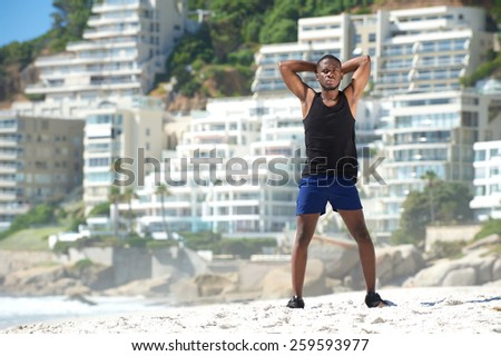Full body handsome young sports man standing at the beach - stock photo