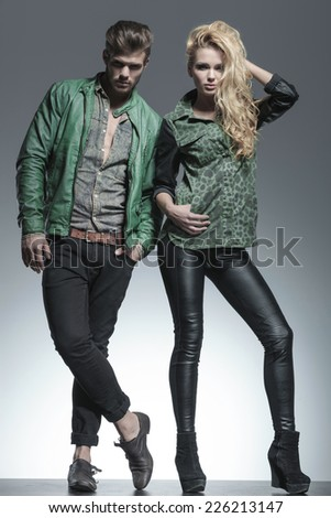 Full body image of a fashion couple posing for the camera, the woman is fixing her hair while the man is holding one hand in pocket. - stock photo