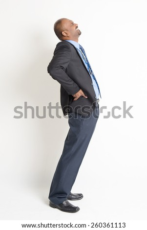 Full body Indian businessman backache, holding his spine with painful face expression, standing on plain background. - stock photo