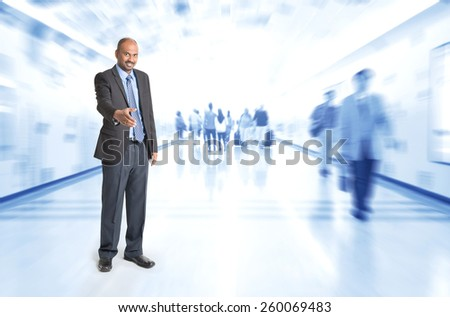 Full body Indian businessman offering hand shake at corridor, inside business building with motion blurred people as background. - stock photo