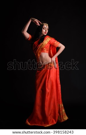 Full body Indian girl in red sari costume standing isolated on black background. Beautiful Indian girl in traditional Indian sari. beautiful indian woman wearing traditional sari studio portrait. - stock photo