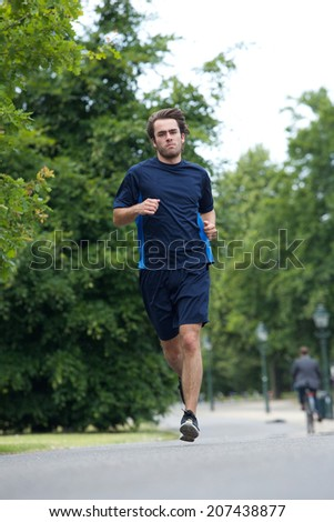 Full body of a young man jogging outdoors - stock photo