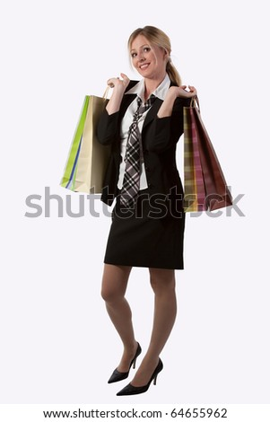 Full body of an attractive blond woman in business suit holding shopping bags standing on white - stock photo