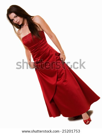 Full body of an attractive young brunette woman wearing a long formal red satin gown holding up showing cute red shoes - stock photo