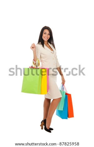 Full body of tall young brunette woman in professional business suit standing holding colorful shopping bags in hands isolated over white background. - stock photo