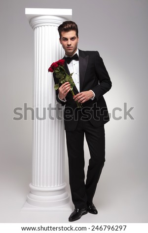 Full body picture of a elegant business man holding a bouquet of red roses in his hands while leaning on a white colomn - stock photo