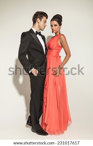 Full body picture of a elegant fashion couple embracing, the man is holding one hand in pocket. - stock photo