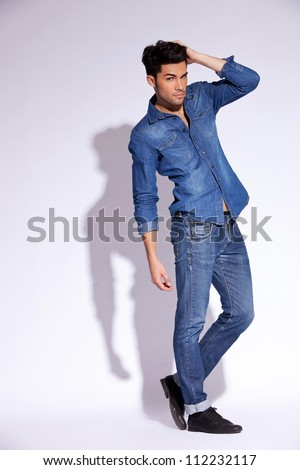 full body picture of a fashion young man with his hand on head - stock photo