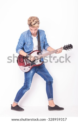 full body picture of a guitarist playing his instrument on white background - stock photo