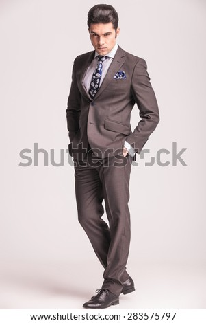 Full body picture of a handsome young business man looking at the camera while holding his hands in pockets. - stock photo