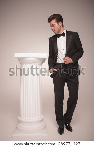 Full body picture of a handsome young business man pulling his jacket while looking to his side. - stock photo