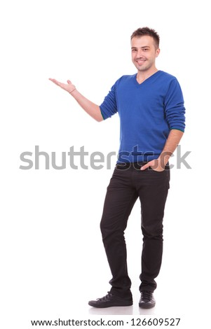 Full body picture of a happy young casual man presenting something - stock photo