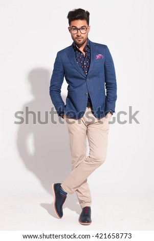 full body picture of a young business man posing with legs crossed in studio - stock photo