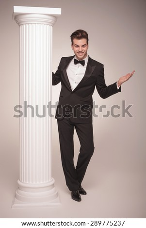 Full body picture of a young elegant business posing with his arms open near a white column. - stock photo