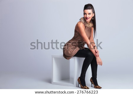 Full body picture of a young elegant fashion woman sitting on a chair while smiling and looking up. - stock photo