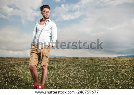 Full body picture of a young man posing in a field full of flowers, looking away with his hands in his pockets. - stock photo
