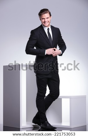 Full body picture of an attractive business man closing his jacket while smiling for the camera.  - stock photo