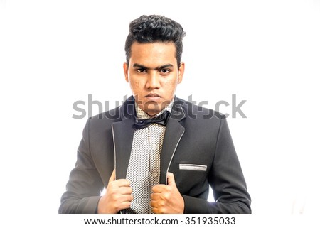 full body picture of an elegant man in tuxedo unbuttoning his coat on white background - stock photo