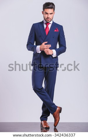full body picture of handsome man in suit with legs crossed while touching hands - stock photo
