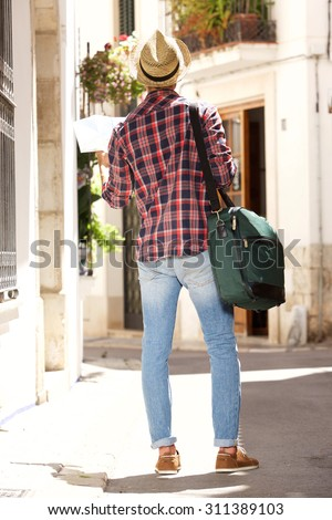 Full body portrait from behind of a traveling man with bag and map - stock photo