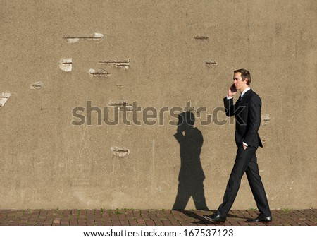 Full body portrait of a business man walking and talking on cellphone - stock photo