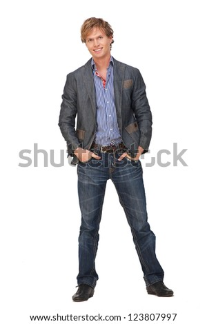 Full body portrait of a casual Caucasian man isolated on white background. He is smiling and has his hands in his pockets. - stock photo