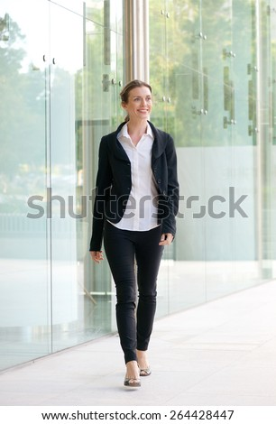 Full body portrait of a happy business woman walking outside office building - stock photo