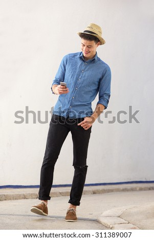 Full body portrait of a smiling young handsome man walking and looking at mobile phone - stock photo