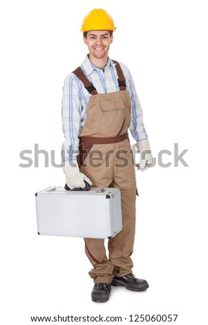 Full body portrait of a smiling young workman or repairman in dungarees and a hardhat carrying a toolkit isolated on white - stock photo