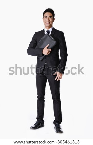 Full body Portrait of a successful young business man carrying a suitcase  - stock photo