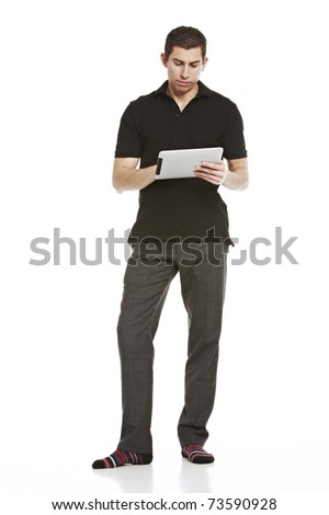 Full body portrait of a young handsome man working on a tablet computer - stock photo