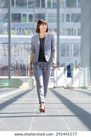 Full body portrait of an attractive professional business woman walking  - stock photo