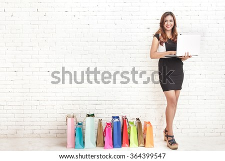 full body portrait of beautiful elegant woman standing next to shopping bags while holding a laptop on white brick wall background - stock photo