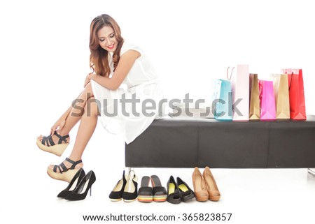 full body portrait of elegant woman sitting next to shopping bags and pairs of shoes isolated on white background - stock photo