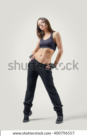 Full body portrait of girl dancer standing in an arrogant pose holding her hands on waist. Front view. - stock photo
